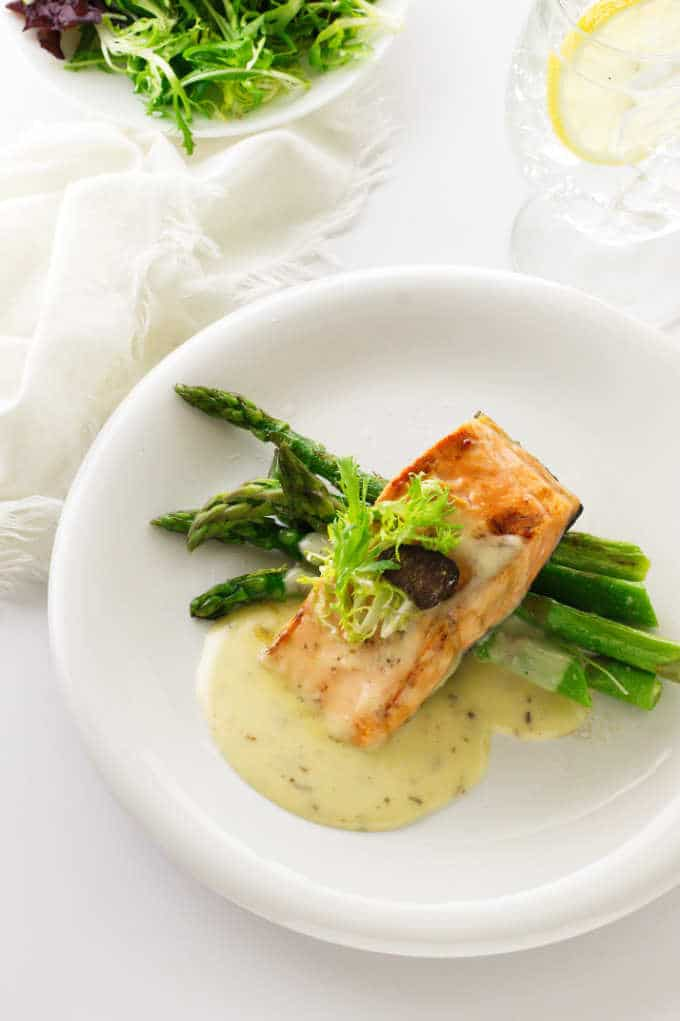 Overhead view of asparagus, salmon and Beurre Blanc sauce, salad, napkin and lemon water in background