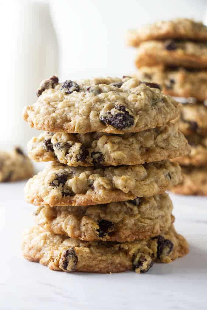A tall stack of oatmeal raisin cookies with milk in the background.