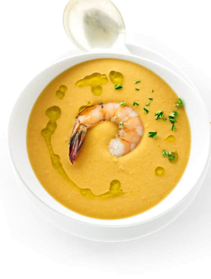 Overhead view of a bowl of creamy shrimp bisque and spoon