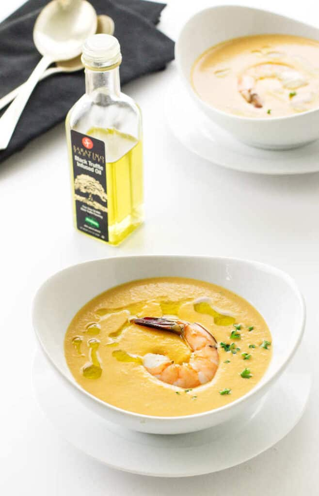 Overhead view of two bowls of shrimp bisque, bottle of truffle oil, napkins and spoons