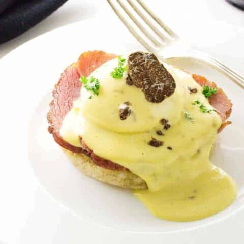 Eggs Benedict with White Truffled Hollandaise Sauce and a slice of a truffle.