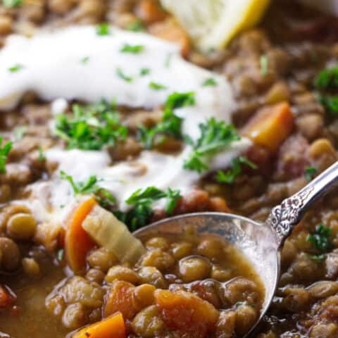 Close up of lentil soup with sour cream and lemon.