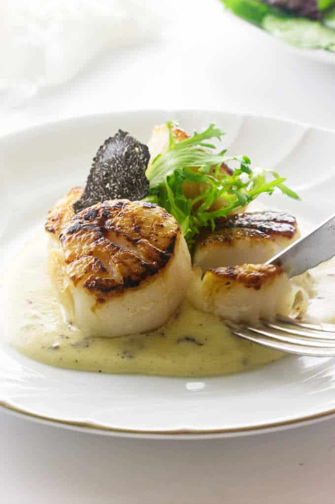 Slicing a seared scallop and dipping it in black truffle sauce garnished with frisée greens and a slice of truffle