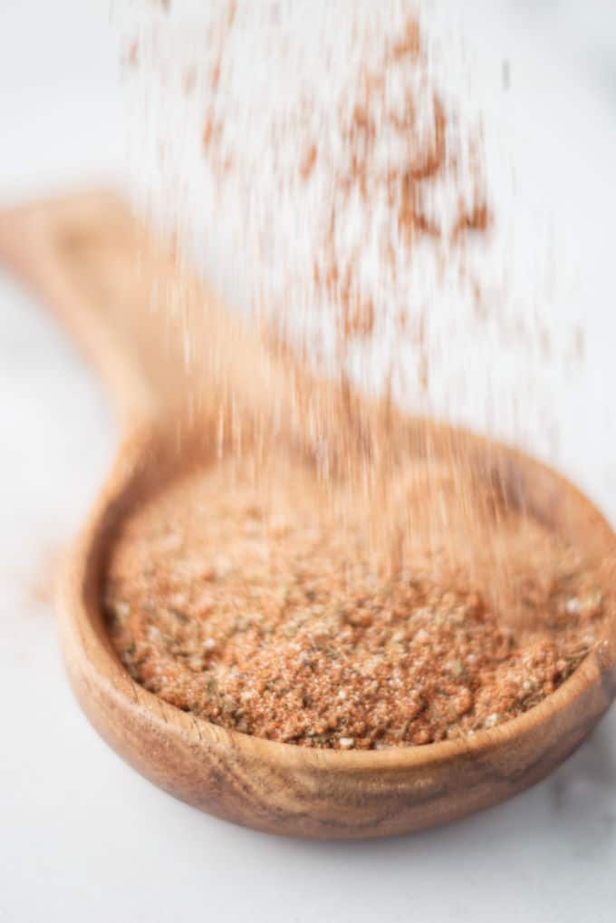 Cajun seasoning mix being sprinkled into a wooden spoon.