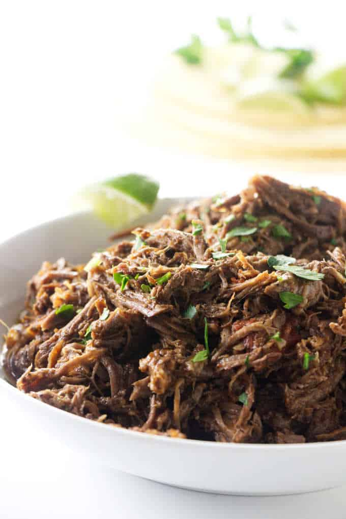 A serving bowl of shredded beef made in the Instant Pot.