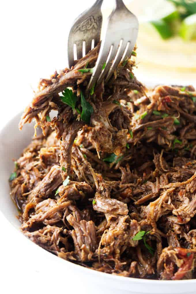 Shredded beef being scooped with a couple of forks.