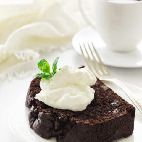 Slice of chocolate loaf cake on a serving plate with fork, coffee and napkin in background