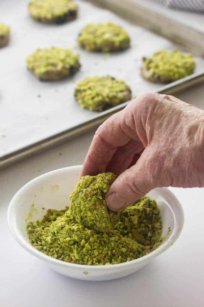 Dipping cookie dough into chopped pistachios.