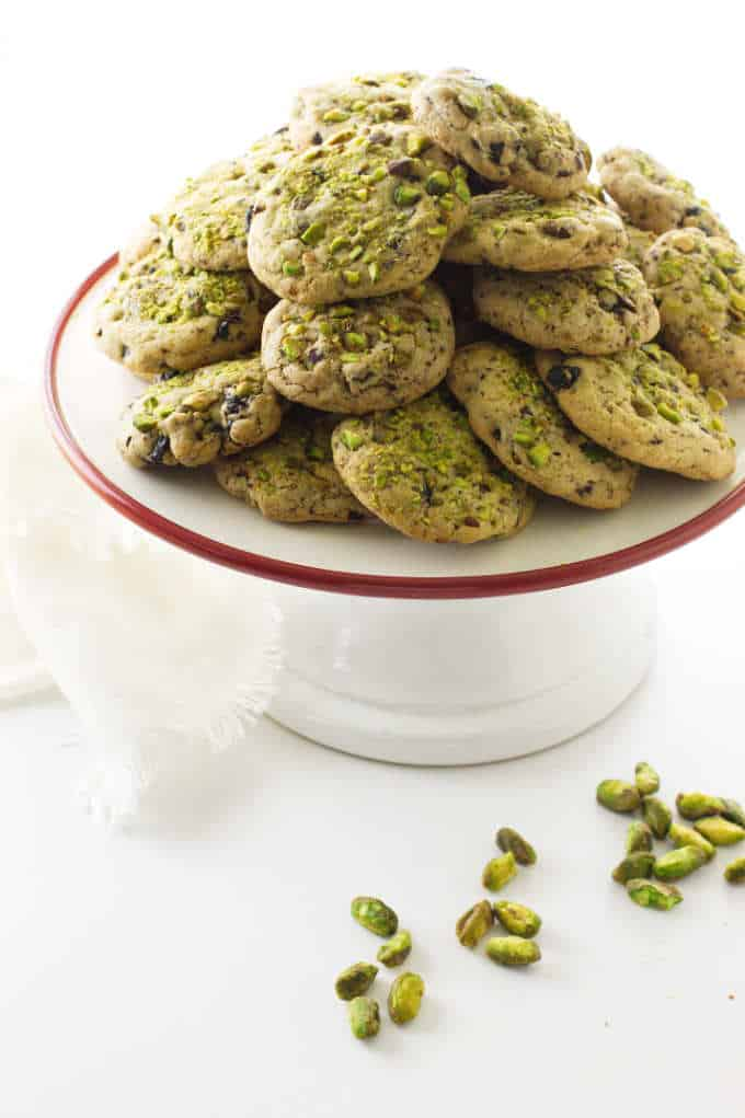 A serving platter with pistachio cherry cookies and some pistachio nuts.