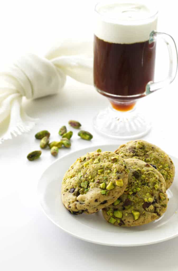 A plate filled with 3 pistachio cherry cookies and a latte drink in the background.
