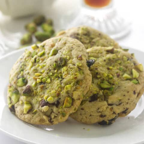 A closeup of pistachio cherry cookies that have dried cherries.