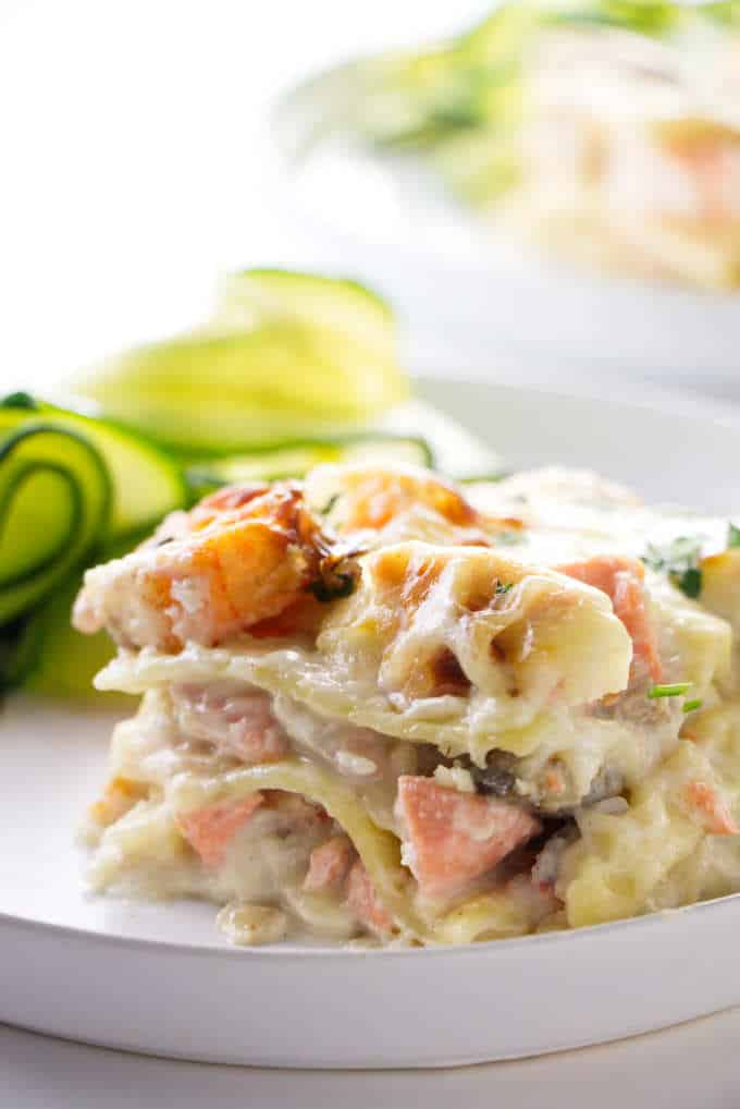 A slice of seafood lasagna with zucchini in the background.