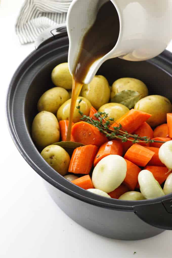 Vegetables in slow cooker with beef broth pouring on