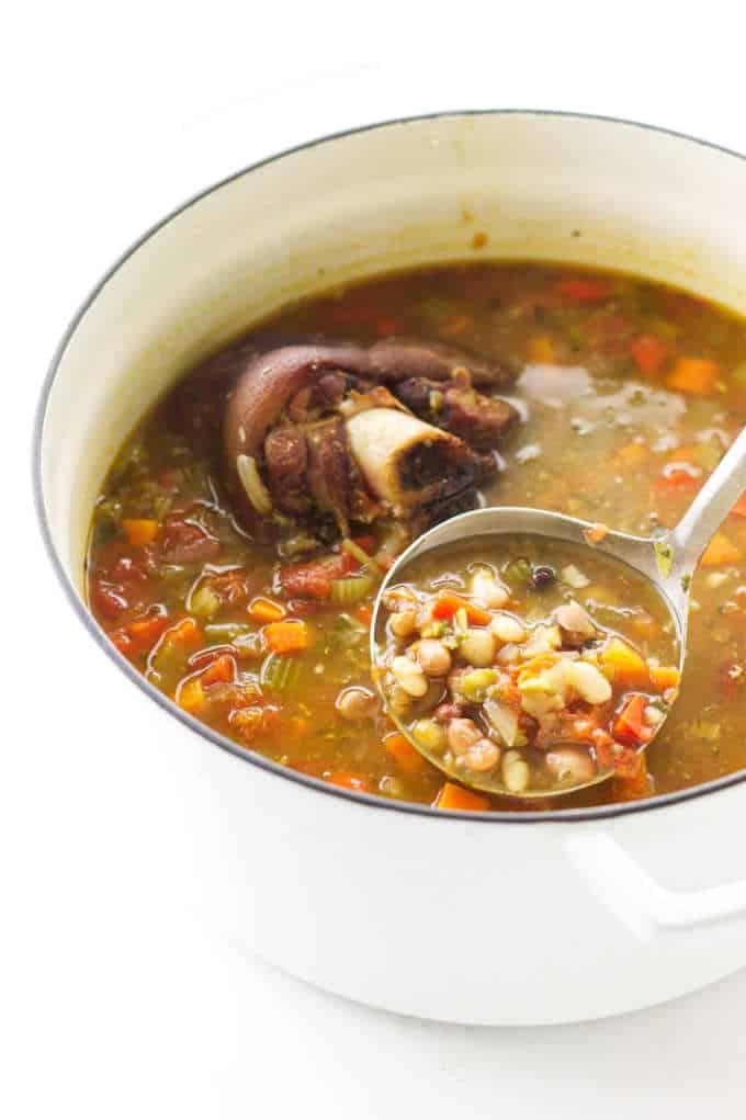 Overhead view of a soup pot of 15 bean soup, ham bone and a ladle of soup