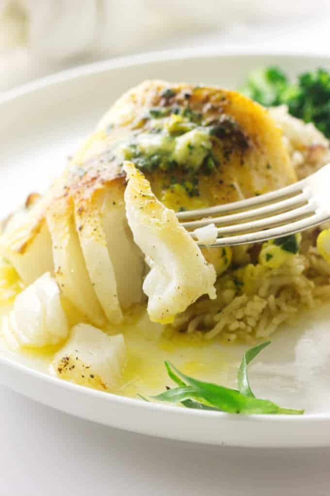 Broiled Pacific Cod with a bite on a fork, melted lemon tarragon butter
