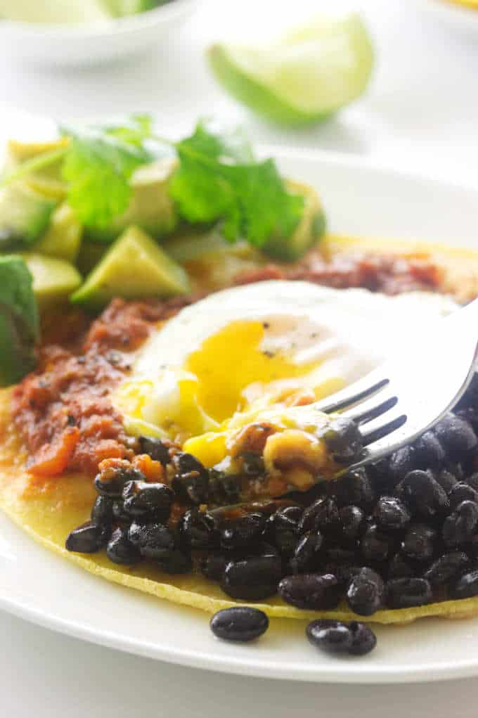Serving of huevos rancheros with a bite on a fork