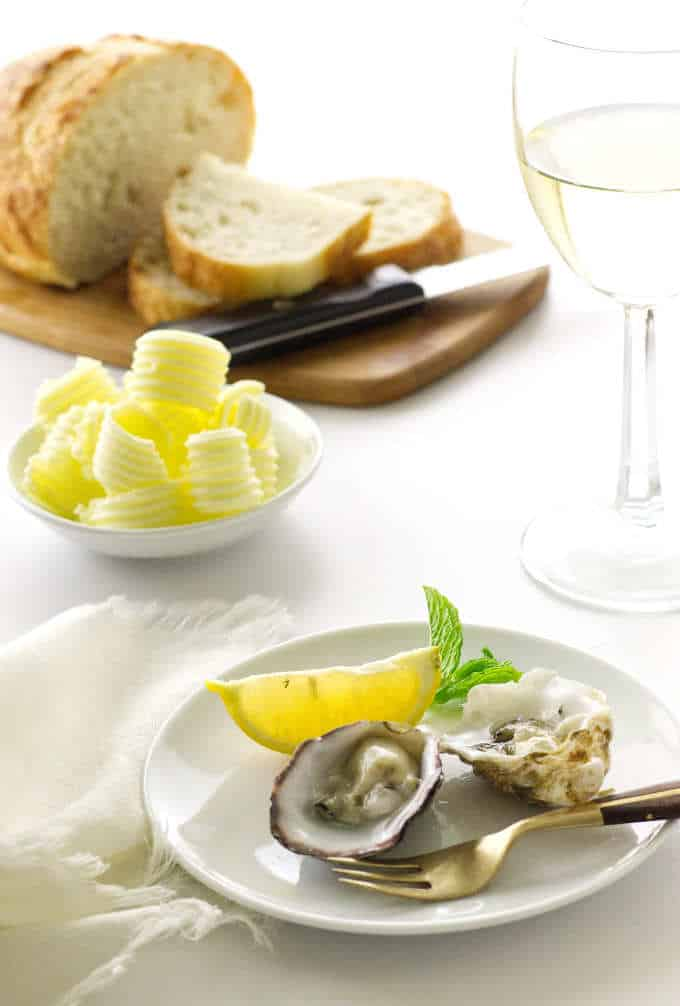 2 oysters on appetizer plate with fork, lemon wedge and mint. Bread, butter curls and glass of wine in background