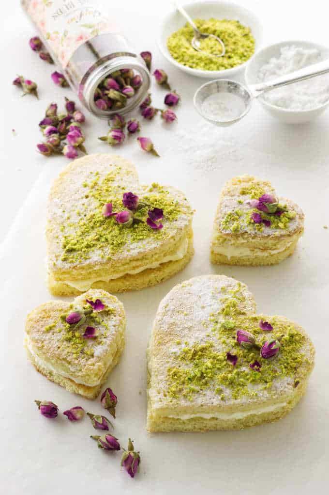Decorated large and small pistachio rose mascarpone cream cakes. Confectioners' sugar, ground pistachios and dried roses in background