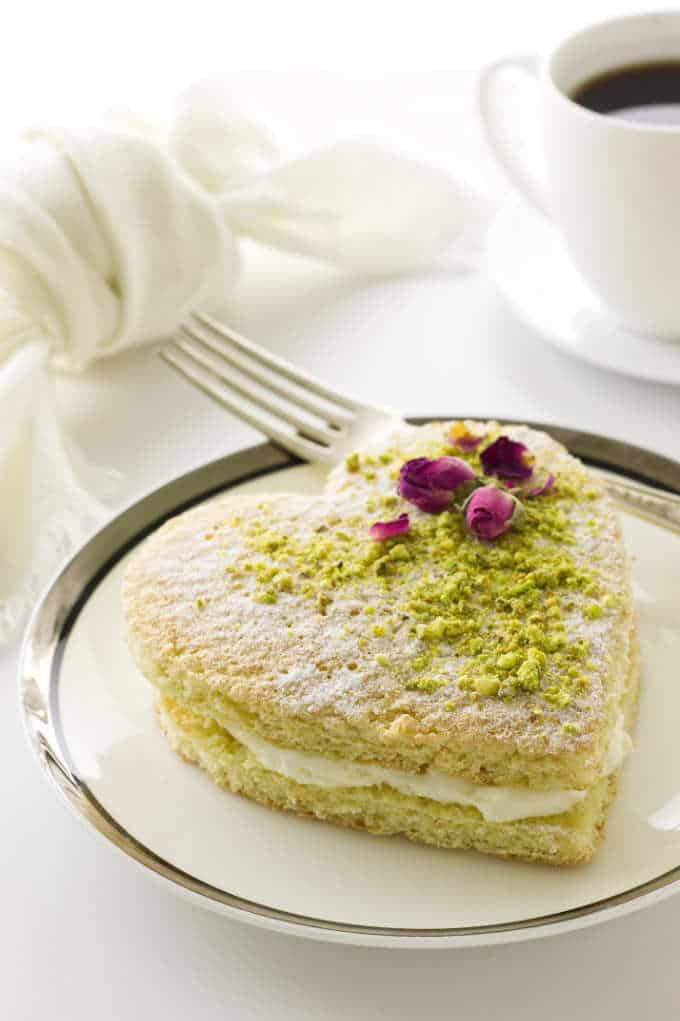 Heart cake dusted with confectioners' sugar and garnished with pistachios and dried roses