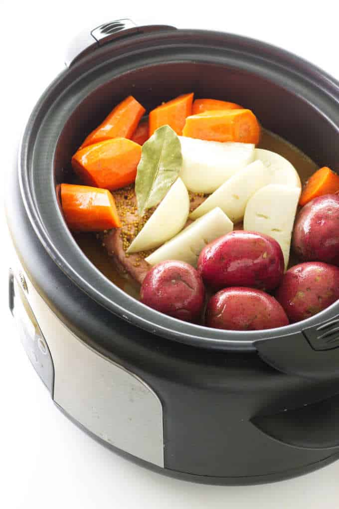 Slow cooker loaded with corned beef, carrots, onions, turnip and a bay leaf