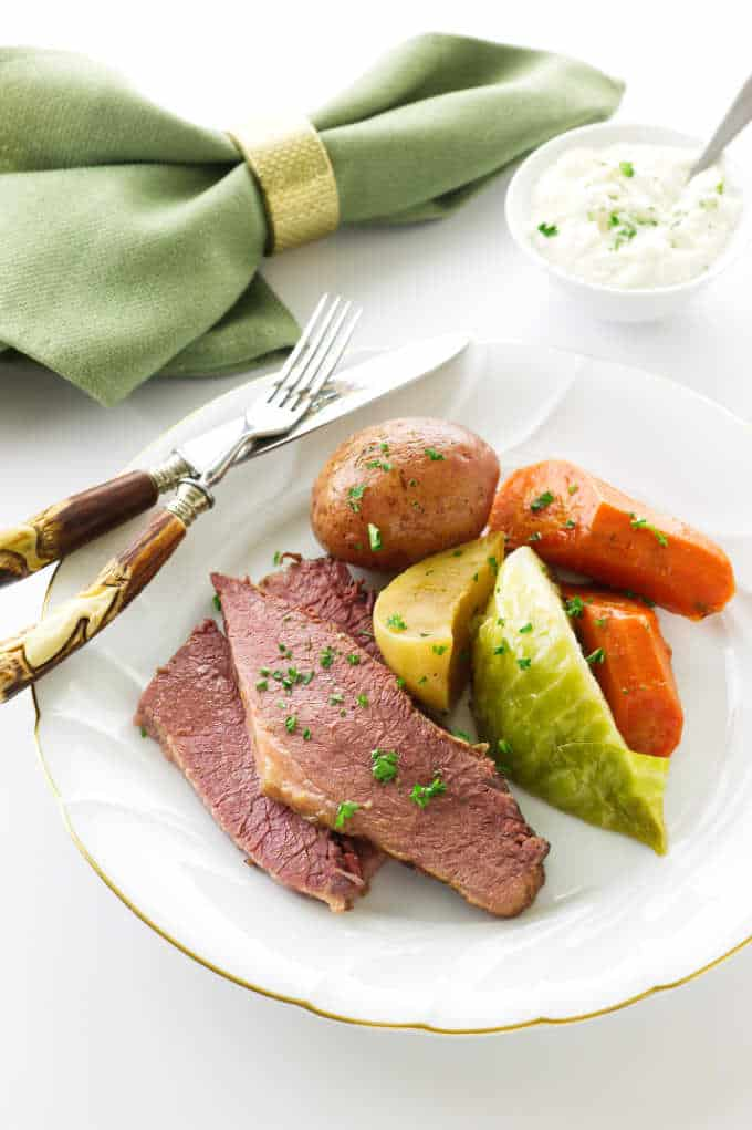Serving of corned beef, cabbage, turnip and carrots. Dish of Fresh Horseradish Aioli Sauce in background
