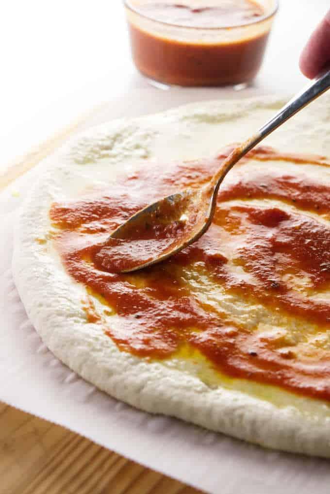 Putting pizza sauce on sourdough pizza dough.