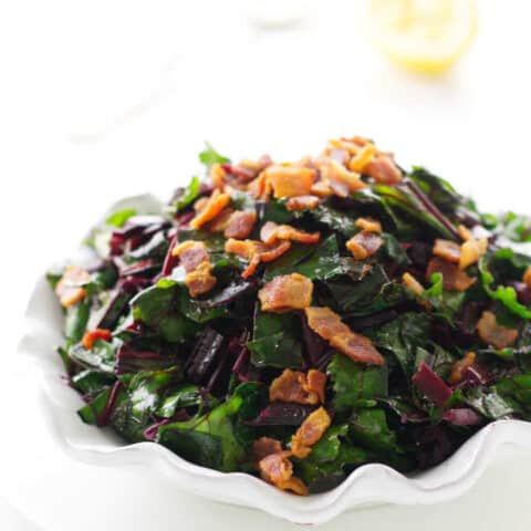 Close up view of side dish of beet greens with bacon bits. Spoon and lemon in background