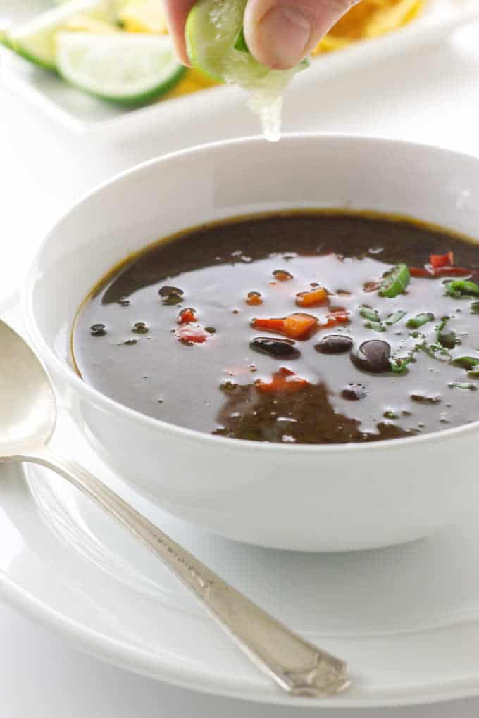Bowl of chipotle black bean soup with lime juice squeezed on top