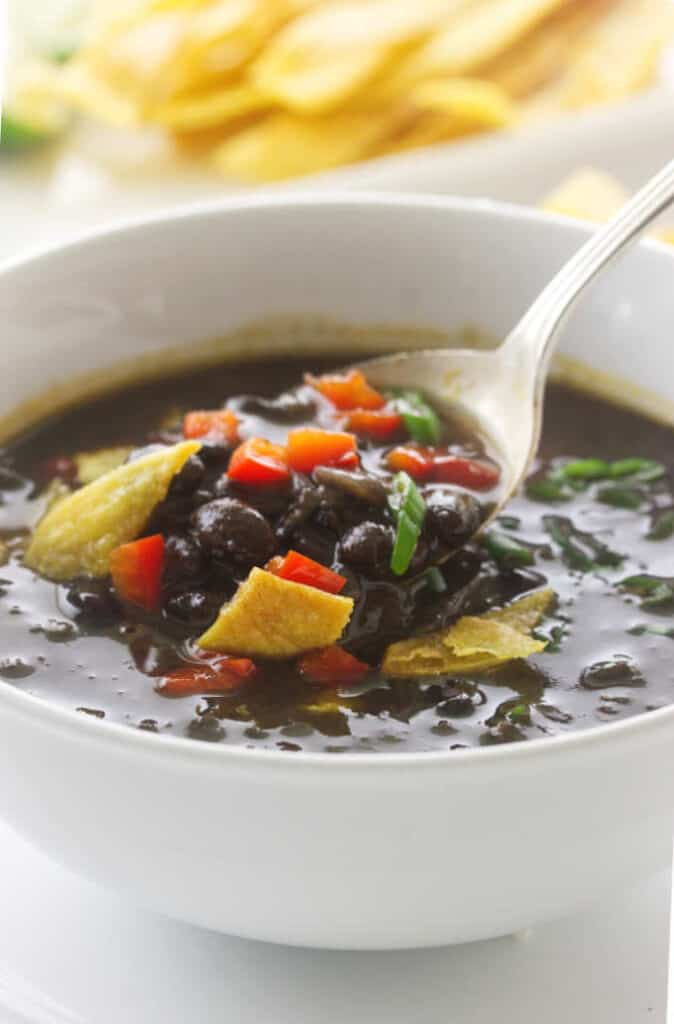 Overhead view of Chipotle Black Bean Soup, garnished with red bell pepper and scallions