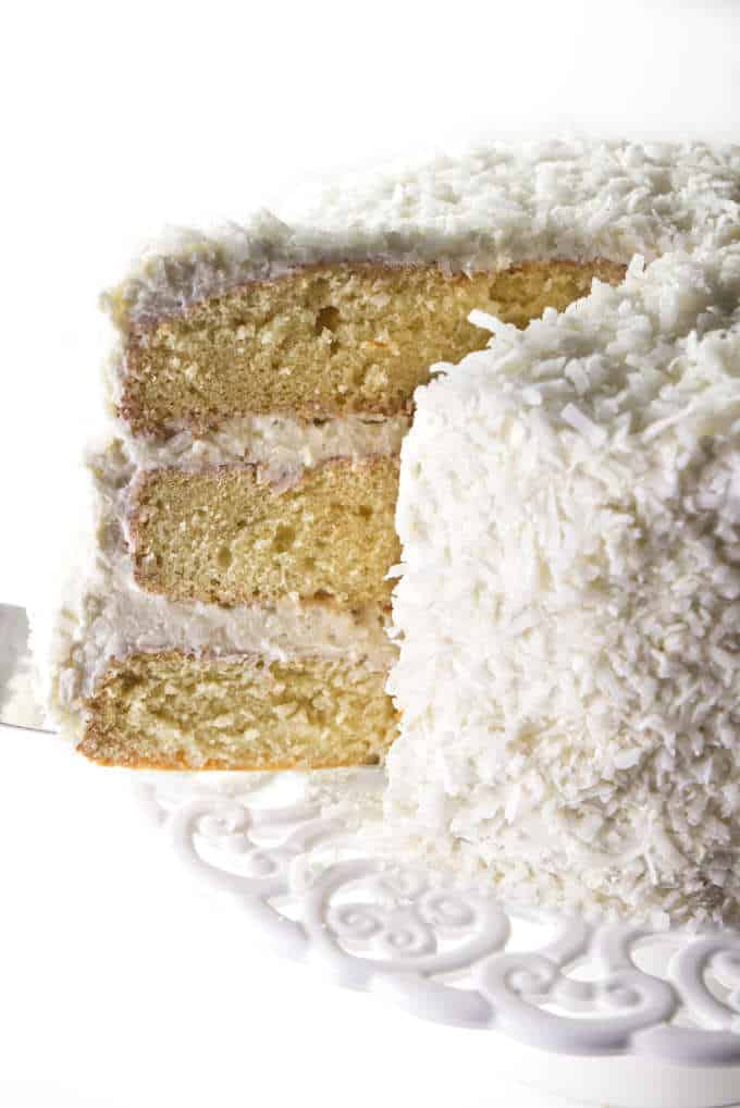 Layered coconut cake with coconut buttercream being served from a cake pedestal.