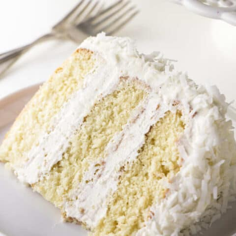 A single slice of coconut cake with coconut buttercream.