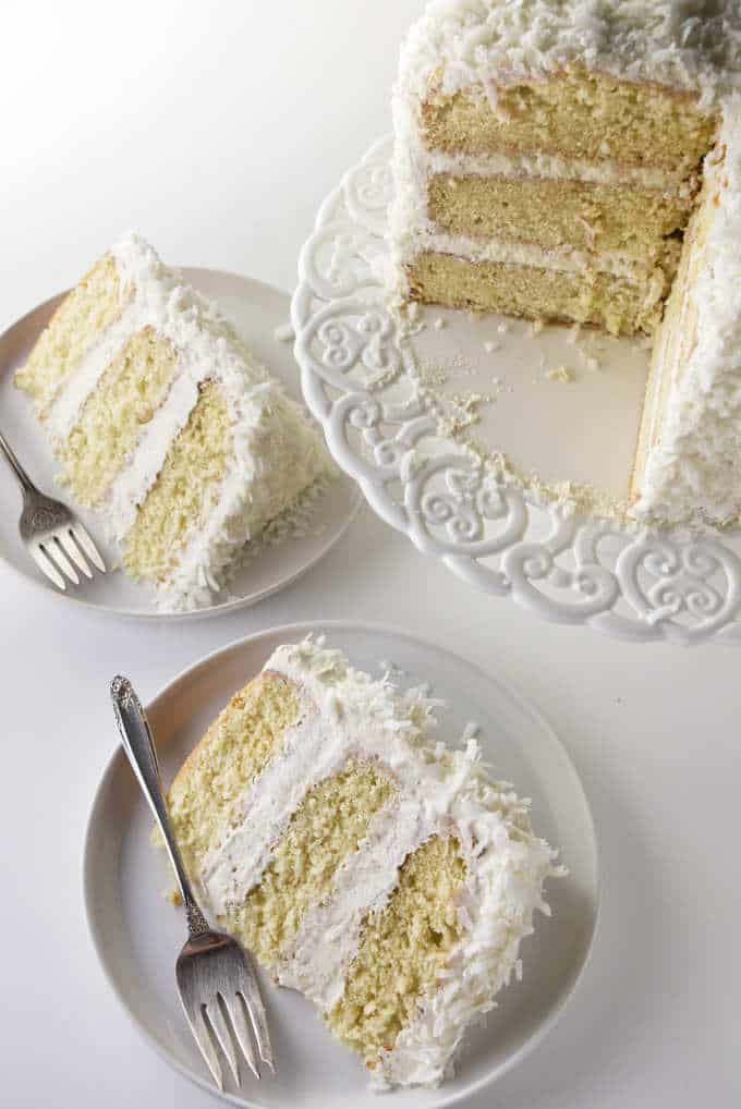 Overhead shot of a layered coconut cake on a cake pedestal along with 2 slices on plates.