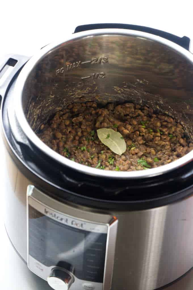 An instant pot with cooked lentils.