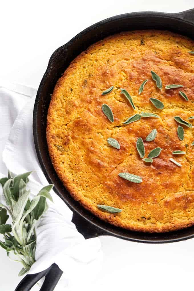 Brown butter skillet cornbread with sage leaves on top.