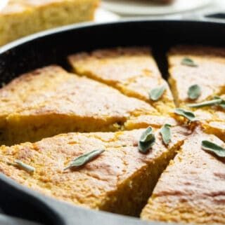 A skillet with sliced cornbread and sage leaves.