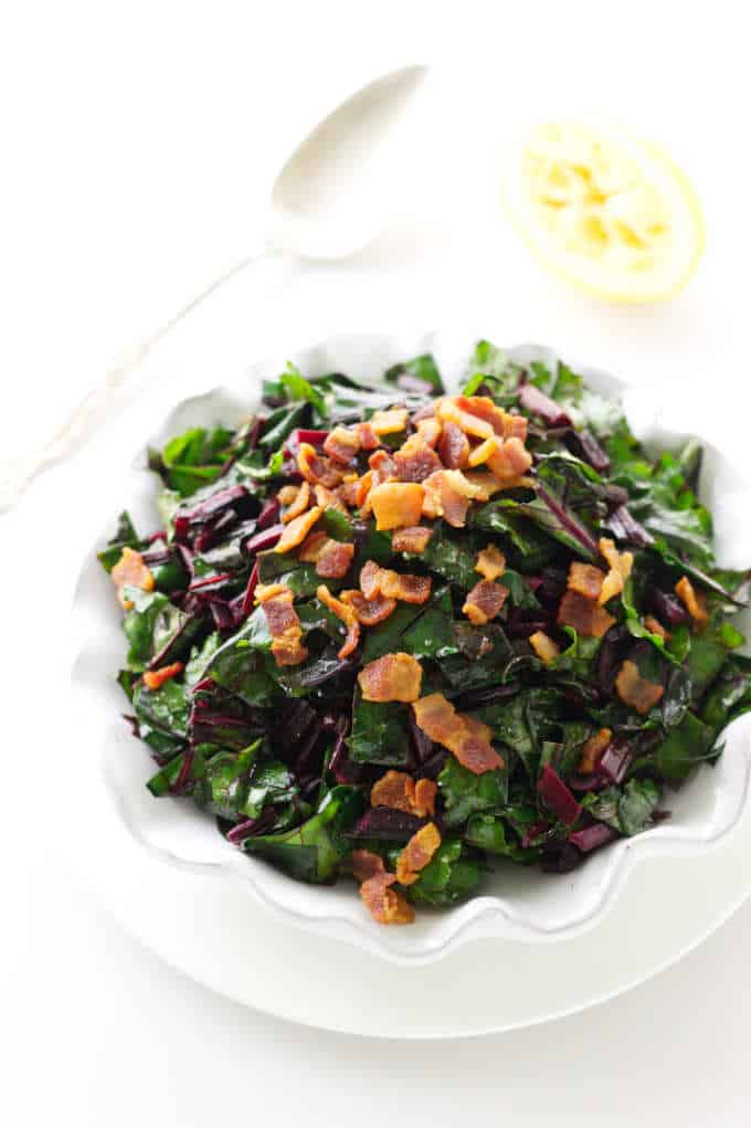 Overhead view of a dish of sautéed beet greens and crisp bacon bits.