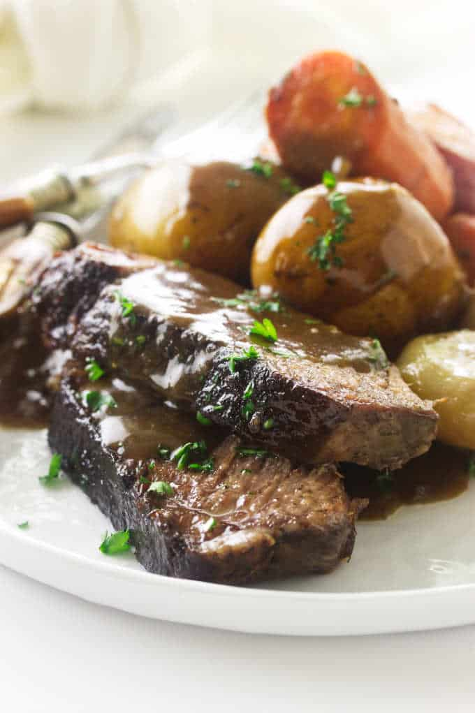 Close up view of a serving of pot roast, potatoes and carrots
