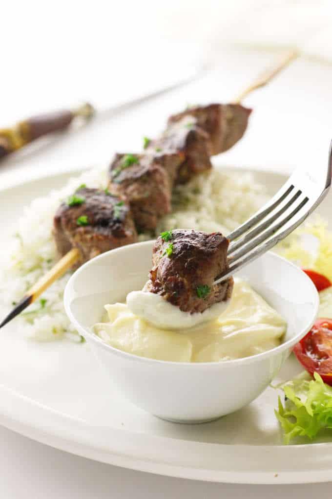Close up view of lamb kabob on a fork dipped in garlic aioli
