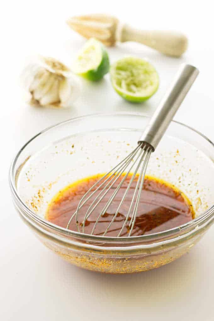 Dish of marinade with whisk. Limes, garlic and juicer in background