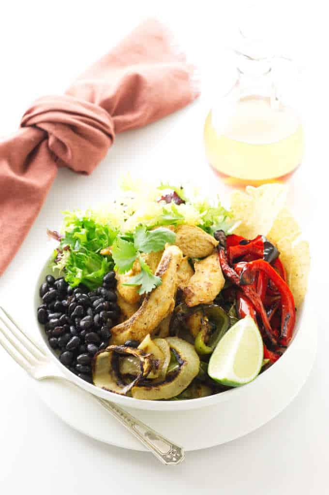 Sheet pan chicken fajita bowl, salad dressing and napkin