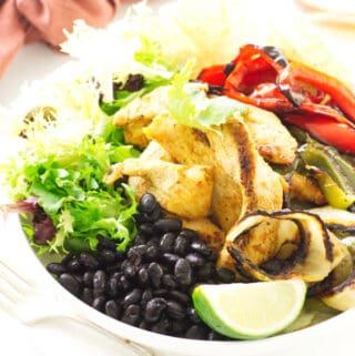 Bowl of black beans, roasted chicken, onions, red/green bell pepper and lime wedge