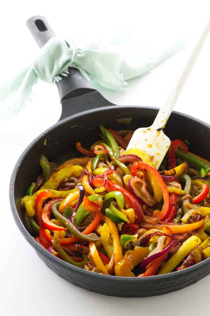 Skillet with fajita vegetables and a spatula