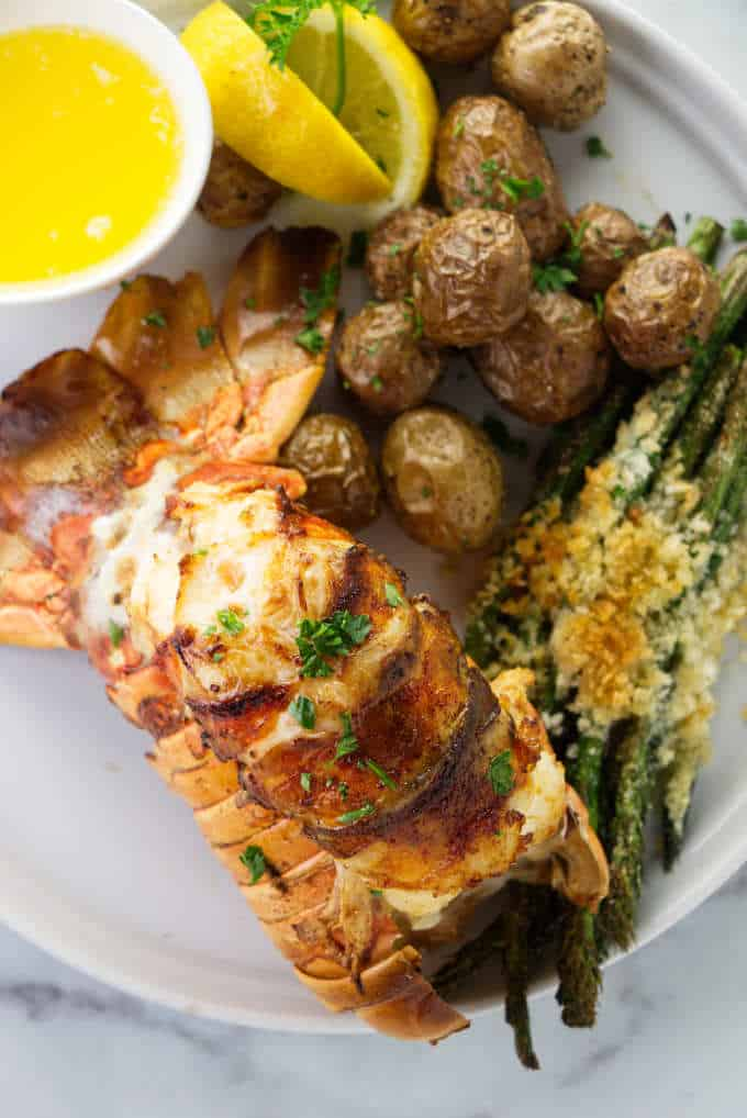 Broiled lobster tail on a plate with potatoes and asparagus.