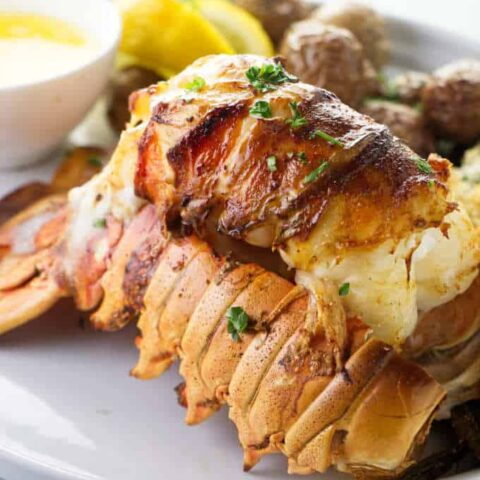 Broiled lobster tail on a serving plate.