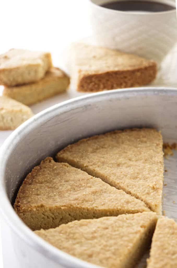 A pan of oatmeal shortbread with coffee in the background.
