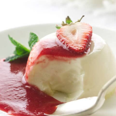 Panna cotta serving with spoon and bite, puddle of strawberry sauce