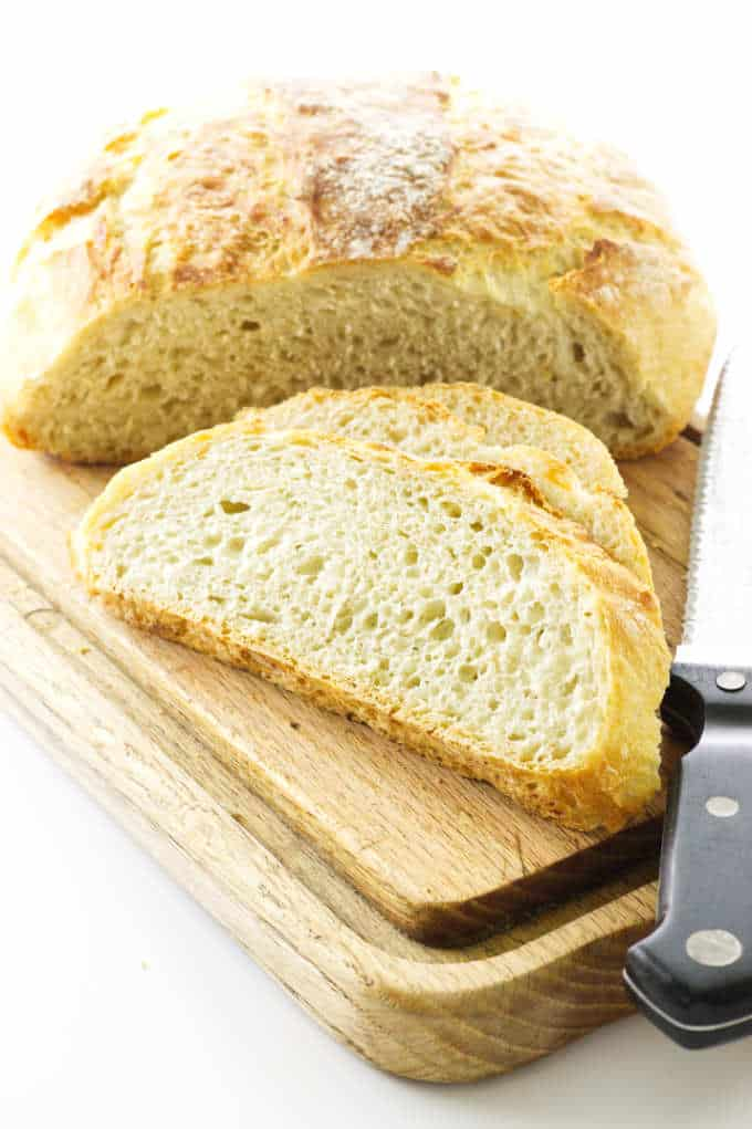 Bread on a cutting board with slices and a knife