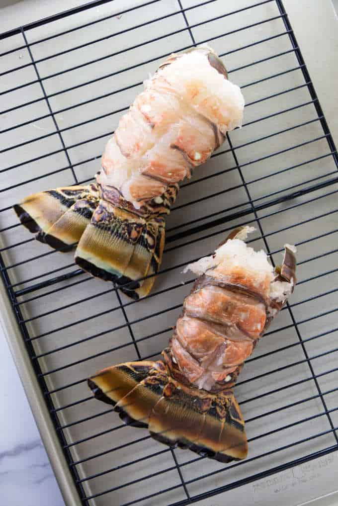Two raw lobster tails ready to be broiled.