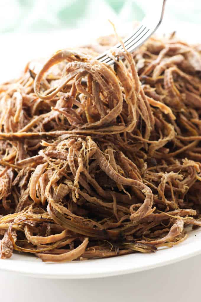 Close up view of a platter of shredded tri-tip and a fork lifting the shredded meat