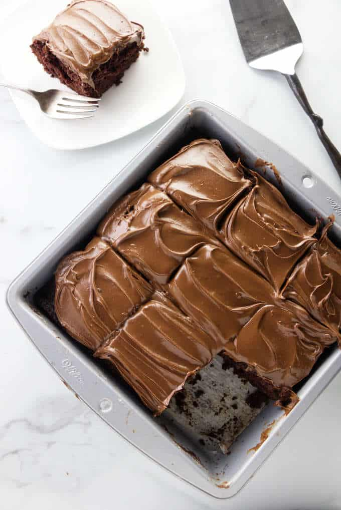 A pan with slices of wacky chocolate cake frosted with chocolate peanut butter frosting.
